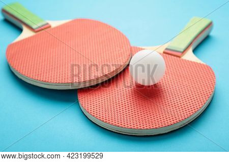 Ping Pong Rackets And Ball On Blue Background. Top View