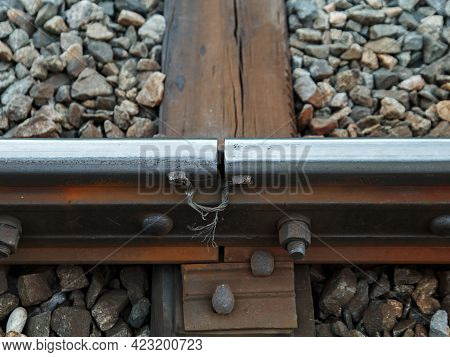 Junction Of Two Rails On Railway On Track With Wooden Sleepers And Stones.
