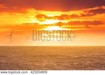 Renewable Green Electricity Wind Power Generation Offshore. Sunrise At Decarbonization Industry Wind