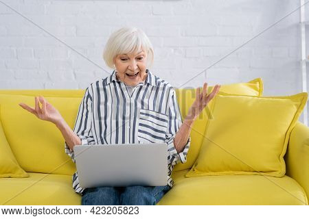 Astonished Woman Using Laptop In Living Room.