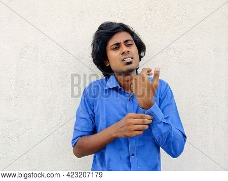 Young South Indian Business Man Buttoning One Side Sleeve Of A Blue Shirt. Other Side Folded Sleeves