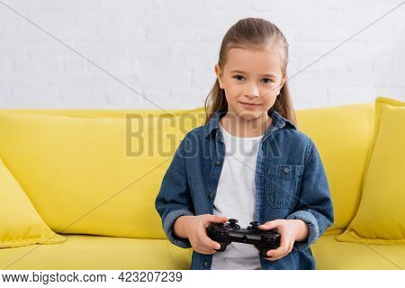 Kyiv, Ukraine - January 11, 2021: Kid With Gamepad Looking At Camera On Couch.