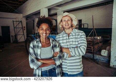 Mixed Race Farmers Standing With Crossed Arms Smiling In Farm Stable