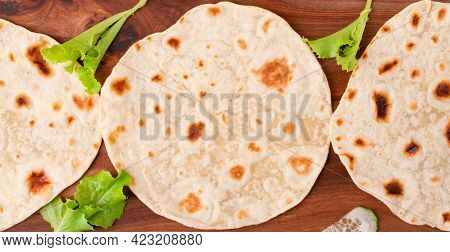Three Tortilla Flatbreads On The Wooden Board. Toned Image