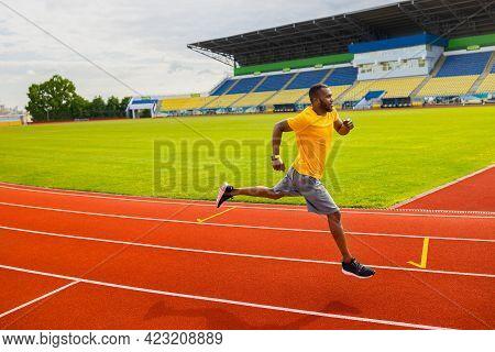 Professional Focused Afro American Athlete Runner Training Running On Racetrack At Stadium. Side Vie