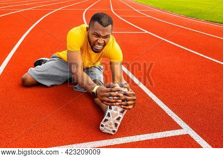 Young Focused Attractive African American Athlete Sportsman Stretching On Racetrack At City Stadium.