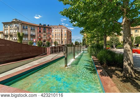 Modern fountain on town square with green trees under blue sky in Alba, Piedmont, Northern Italy.