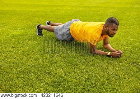 Side View Of Fit Confident Afro American Athlete Sportsman Doing Plank Exercise On A Grass Field, Yo