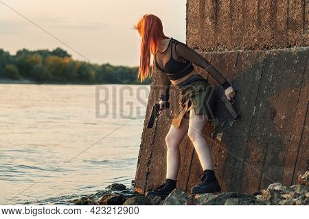 Outdoor Portrait Beautiful Sexy Redhair Girl With Two Pistols Posing On The Beach Of Riverbank