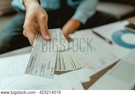 Businessman Or Manager Hands Giving Cheque To Colleague. Business, Finances And Money Concept
