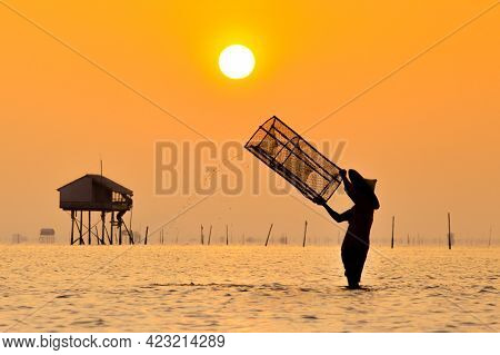Silhouette Of Fisherman Shooting Sunset Scene In The Water.