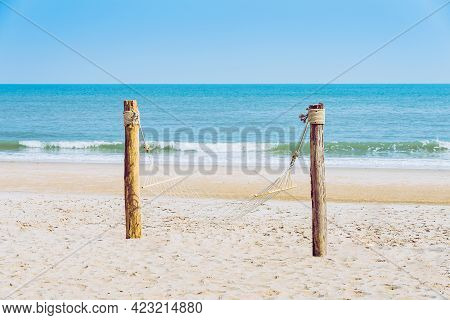 Empty Cozy Hammock Made Of Mesh Hang On Wooden Poles On The Tropical White Beach For Tourists. Summe