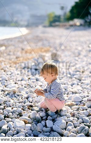 Kid Sits On A Pebble Beach And Holds A Pebble In His Hand. Side View