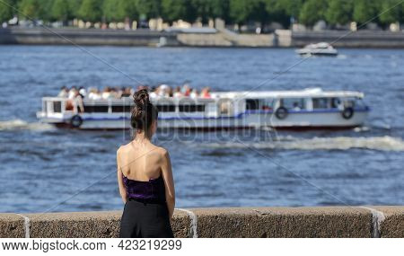 A Girl In Summer Clothes With Open Shoulders Stands On The River Embankment, Dvortsovaya Embankment,