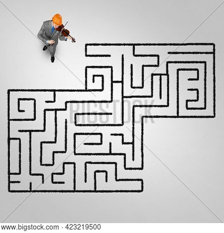 Top View Of Businessman Playing Violin And Drawn Labyrinth On Floor