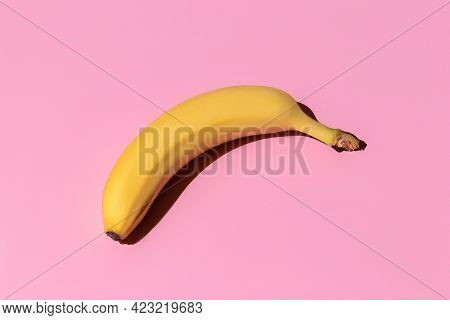 Ripe Yellow Bananas Isolated On A Pink Background. Hard Shadows From The Sun At Noon. Travel And Ent