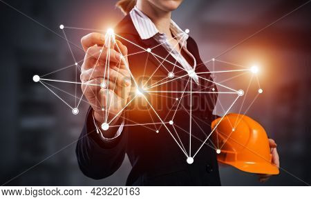 Businesswoman Pointing On Abstract Network Structure. Woman Engineer In Business Suit Holding Safety