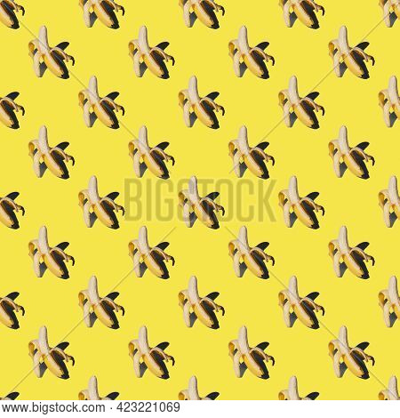 Pattern With Ripe Peeled Yellow Banana Isolated On A Bright Background. Hard Shadows From The Sun At