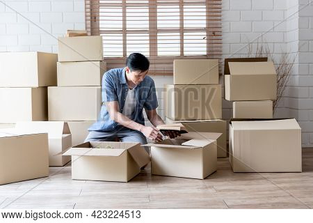 Asian Handsome Man Is Packing Things, Such As Books, Into Boxes For Relocation To New Home, To Peopl