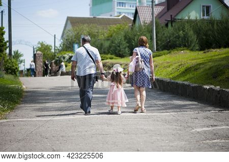 Family Walking In The Park. Mom Dad And Little Girl Walking Holding Hands. Back View. Daughter In A