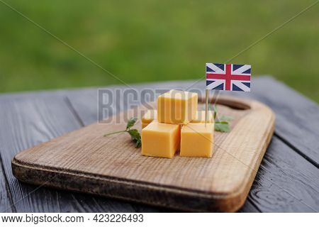 British Cheddar Cheese Cubes On Wooden Board With United Kingdom Flag. Mans Hand Places Toothpick Wi