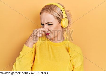 Young blonde woman listening to music using headphones smelling something stinky and disgusting, intolerable smell, holding breath with fingers on nose. bad smell