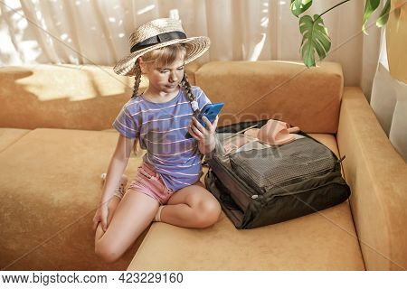 Pretty Girl In Straw Hat And Sunglasses Sitting Near Suitcase Packed For Vacation And Demonstrates T