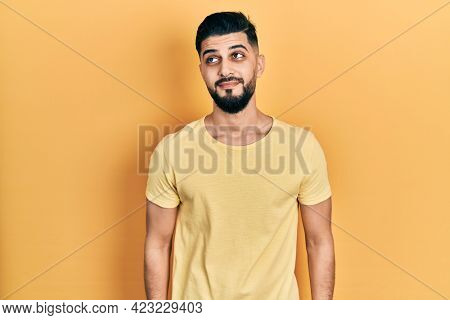 Handsome man with beard wearing casual yellow t shirt smiling looking to the side and staring away thinking.