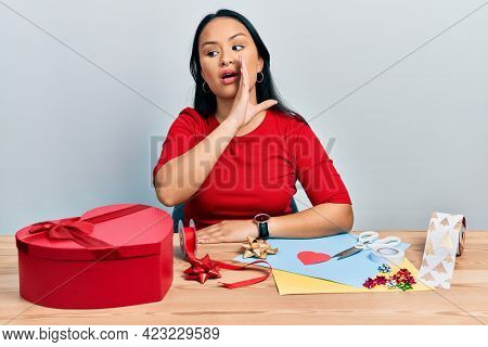 Beautiful hispanic woman with nose piercing doing handcraft creative decoration hand on mouth telling secret rumor, whispering malicious talk conversation