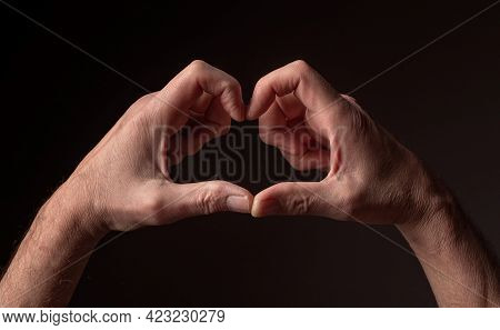 Heart-shaped Mature Male Hands As Peace And Hope Sign Over Black Background.