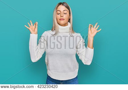 Beautiful blonde woman wearing casual turtleneck sweater relax and smiling with eyes closed doing meditation gesture with fingers. yoga concept.