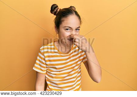 Beautiful little girl wearing casual striped t shirt smelling something stinky and disgusting, intolerable smell, holding breath with fingers on nose. bad smell