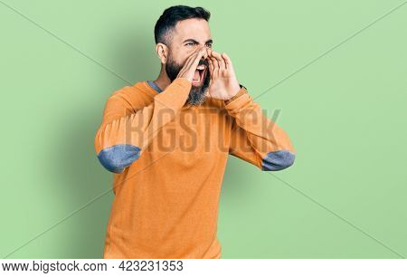 Hispanic man with beard wearing casual winter sweater shouting angry out loud with hands over mouth