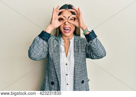 Young hispanic woman wearing business clothes doing ok gesture like binoculars sticking tongue out, eyes looking through fingers. crazy expression.