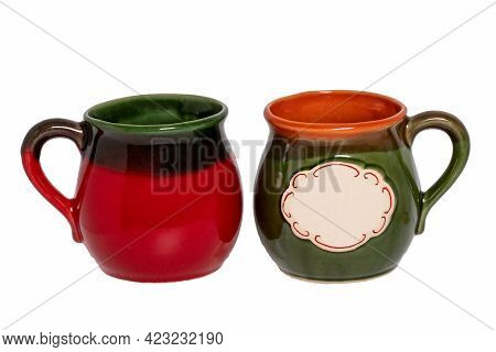 Mug For Coffee. Closeup Of A Empty Red Green And A Green Orange Ceramic Cup With An Empty White Labe