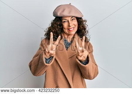 Middle age hispanic woman wearing french look with beret smiling looking to the camera showing fingers doing victory sign. number two.