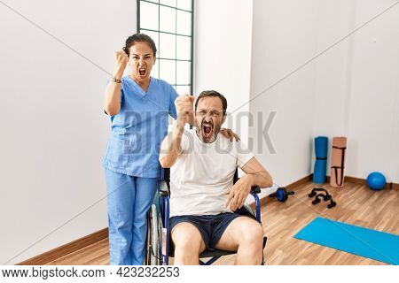 Hispanic middle age man sitting on wheelchair and nurse at rehabilitation clinic annoyed and frustrated shouting with anger, yelling crazy with anger and hand raised