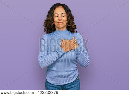 Middle age hispanic woman wearing casual clothes smiling with hands on chest with closed eyes and grateful gesture on face. health concept.