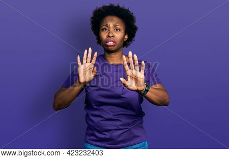 African american woman with afro hair wearing casual purple t shirt moving away hands palms showing refusal and denial with afraid and disgusting expression. stop and forbidden.