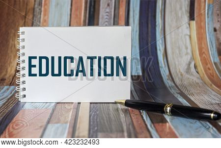 The Word Education Is Written On A Notepad And On A Striped Background.