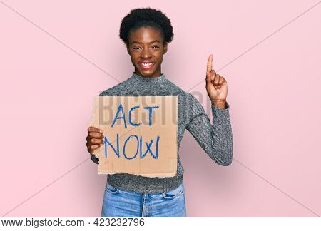 Young african american girl holding act now banner surprised with an idea or question pointing finger with happy face, number one
