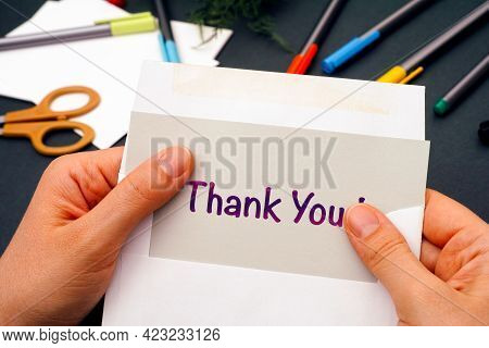 Woman Hands Taking Out Gray Paper With Words Thank You From Envelope. Office Supplies On Background.