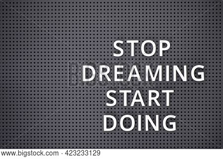 Phrase Stop Dreaming Start Doing Spelled Out With White Letters On Gray Pegboard