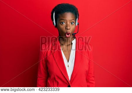 Young african american girl wearing call center agent headset scared and amazed with open mouth for surprise, disbelief face