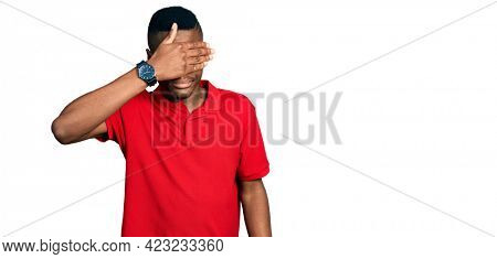 Young african american man wearing casual red t shirt covering eyes with hand, looking serious and sad. sightless, hiding and rejection concept