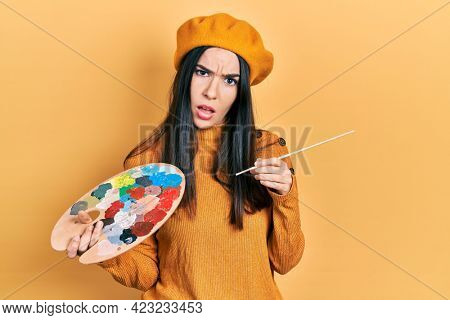 Young brunette woman holding paintbrush and palette wearing beret in shock face, looking skeptical and sarcastic, surprised with open mouth