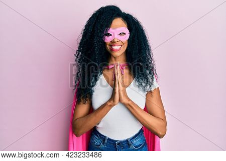 Middle age african american woman wearing super hero costume praying with hands together asking for forgiveness smiling confident.