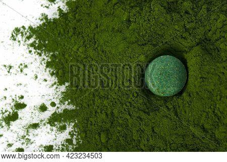 Spirulina Pill Tossed Into Spirulina Powder Scattered On White Background