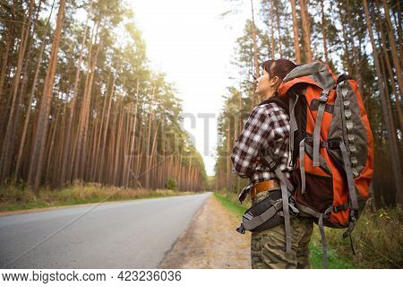 Tired Female Tourist Walking On The Roadside With Big Backpack. Domestic Tourism, Independent Travel