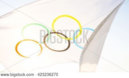 The Olympic Flag Flutters In The Wind Against The Background Of The Sky And The Sun In Close-up. The